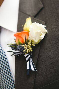 With the trend of mismatched bridesmaid dresses, there are plenty of options to mix and match his style with summer's bold colors and prints too. Both the bright orange rose and navy striped ribbon in this groom's boutonniere add a summery pop to this his charcoal suit.
