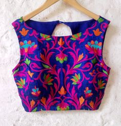 This Blue Silk Blouse has an overall Folk feel brought out by the colorful embroidery pattern. The Front has All over Floral Embroidery in Pink,