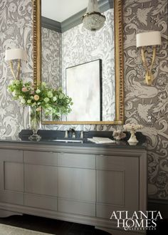 "Designer Jessica Bradley aded warmth to this spacious formal powder room with Lewis & Wood's ornate wallpaper in ""Bacchus,""complementing the pattern with an equally old-world Italian gilt mirror and an antique tufted chair. #bathroom #wallpaper"