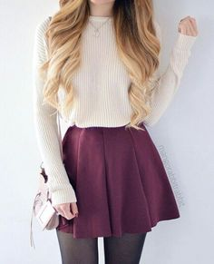 A white sweater, with a maroon skater skirt and black stockings.