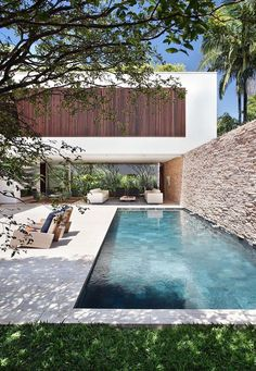 Swimming pool in a contemporary, minimalistic setting, in front of a stone wall