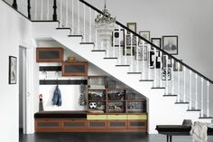 Under stair storage. Love the railing and art as well.