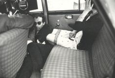 """Jean-Luc Godard snuggled up against Brigitte Bardot's legs during the filming of """"Contempt"""", 1963."""