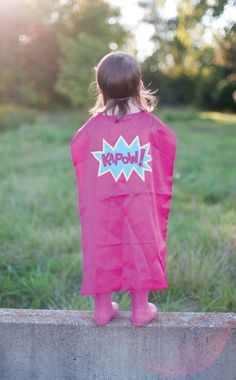 This Kapow cape comes in hot pink satin with a lilac & pink KAPOW! Comes with matching elastic mask, 2 pc set.