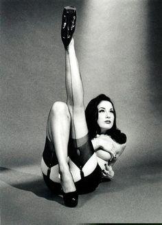 Dita Von Teese black and white portrait in classic stockings pose.
