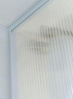 簡単DIY・二重窓の作り方 突っ張り棒を上下2本突っ張り、真ん中のやや奥にもう一本突っ張って、隙間にプラダンを差し込む。
