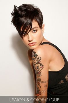 Rock star style! Smooth, side-swept bangs bring a nice contrast to the texture at the crown of this jet-black pixie cut.