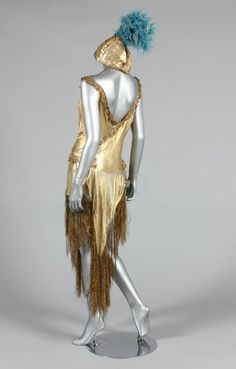 A beaded cloth of gold dance/cabaret outfit, 1920s, the matching turban labelled 'A Fonnesbech, Copenhagen', the dress trimmed with gold bobbin-lace, th skirt with ornate rhinestone studded and beaded centre-panel, the matching turban with feather and tulle cockade, bust 92cm, 36in (2) Provenance: Henning Thorsen collection