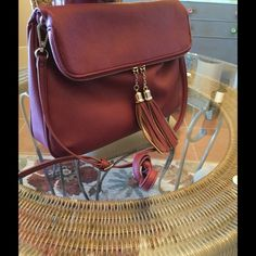 Beautiful Burgundy color shoulder purse Envelope style shoulder bag with 2 tassels at each end of the zipper. It's super cute and stylish. NWOT None  Bags Shoulder Bags