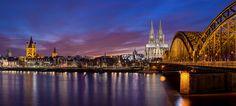Kölner Altstadt Panorama mit Kölner Dom, Hohenzollernbrücke und Groß St. Martin in der blauen Stunde.