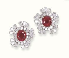 A PAIR OF RUBY AND DIAMOND CLUSTER EAR CLIPS, BY CARTIER   Each set with an oval-cut ruby weighing 5.41 and 6.37 carats within a circular-cut and pear-shaped diamond cluster surround, mounted in 18k gold and platinum  Signed Cartier, no 2.55720