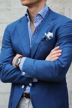 Blue jacket, blue gingham shirt, light grey pants.