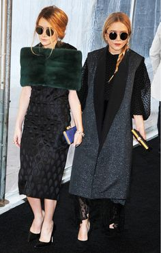 Mary-Kate and Ashley Olsen wear retro-round sunglasses with their oversized sequin coat, black gown, and black classic pumps.