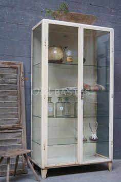 Apothekerskast 10202 - IJzeren apothekerskast met roestige plekken. De kast heeft vier glazen legplanken en boven in de kast drie haken. Het ijzer is crème van kleur.
