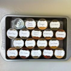 DIY spice rack: plastic jars from the science surplus store, magnets hot glued to the lids, wedding favor labels from the craft store, and a baking tin from the thrift store. When this tin fills up I'll use a larger cookie sheet!