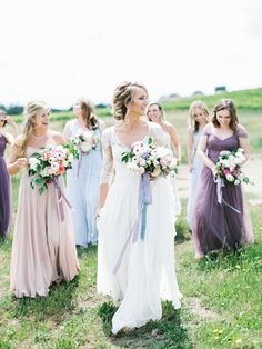 Bridesmaids in mauve, purple, and blue.