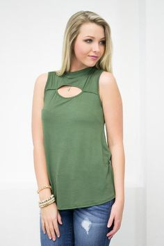 Just imagine yourself wearing this cool sleeveless top on a breezy summer day at the beach. Can't you just feel the salty air on your shoulders. This thin top features a mock neck bind, a cut out fron