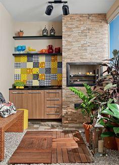 Esta varanda gourmet tem churrasqueira, deque e jardim vertical. Note que os pedriscos foram acomodados ao redor dos deques de madeira. Poupando na escolha de cada elemento, a paisagista Caterina Poli conseguiu encaixar no orçamento um belo painel de azulejos coloridos.
