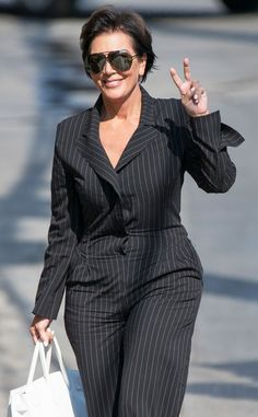 A pinstripe clad Kris Jenner finishes her jumpsuit look with oversized all-black aviators for a chic effect.