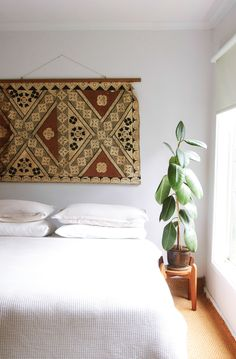 A lovely rug or a piece of fabric, even an old bed spread makes a good headboard. I also like the way it is hung, only 1 heavy  nail into the wall.