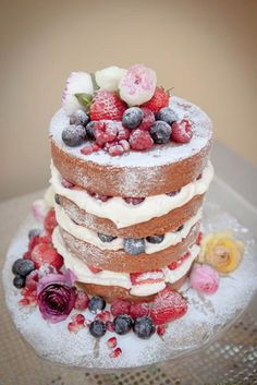 Naked cake with fresh cream, blueberries, strawberries and raspberries by dazzleliciouscakes.co.uk. Photo by Freckle Photography. | Visit wedding-venues.co.uk