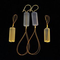 "Alex Stanyon: , Earrings in coldworked Bullseye casting glass (color changing purple to blue and yellow), 14k yellow gold ear wires, and 24k gold plated stainless steel wire. 3"" in length. Glass pieces can be worn together or individually, with the loops up or loops down"