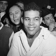Cowboy Rocky Lee squeezed his arm around Joe Louis' head and leaned into the ropes, then steered him toward the other side of the wrestling ring. The portly grappler in all-black reared back and fired off a theatrical punch to Louis' face. African American Heroes, Boxing History, Joe Louis, Boxing Fight, Sport Icon, Professional Wrestling, Black History, Black Style, Men's Accessories