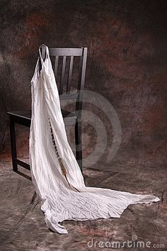 A black chair with a white dress hanging on the corner.