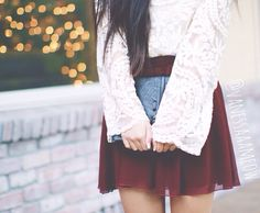 White lace shirt, burgundy skirt, and black leather clutch