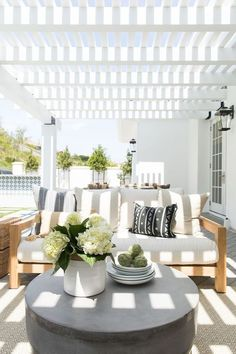 15 Deck Must Haves for Summer Entertaining; white and natural wood outdoor couch, stone coffee stable, white awning.