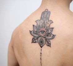A big tattoo on the man`s back always seems effective and mysterious, especially if it's an ancient symbol such as hamsa with an eye, flower and hieroglyphs.