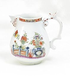 Small Jug with Table Design.   Meissen. Circa 1735.     Porcelain, blue decor painted under glaze, colours and gold over glaze. Height 10,5cm.   Crossed swords marking. Under glaze painter's marking, illegible moulder's marking.