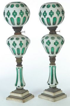 lighting, Continental, A pair of cut overlay Quatrefoil banquet lamps, European, 2nd half-19th century, opaque white cut to green with pear- shape fonts, mounted on cut overlay standards and double-step marble base. Period Kerosene burners and original shades. Circa 1850-1900