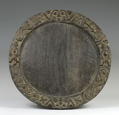 """Nigeria; Yoruba peoples Opon Ifa (divination tray) Wood Diameter 54 cm (21"""") The University of Iowa Museum of Art, The Stanley Collection, X1986.397 Trays like this one are used by the babalawo """"father of secrets,"""" the priest of Ifa divination. The priest begins the divination process by placing the tray on a cloth on the ground and covering it with wood dust or flour. He then shakes sixteen palm nuts in his cupped hands, attempting to catch them in his right hand. If two remain in his left"""