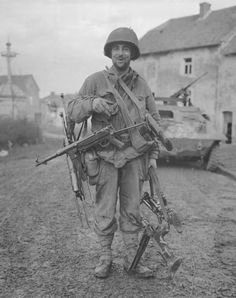 ..U.S. soldier with several captured German sub-machine guns.