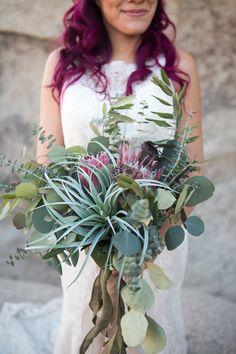 King protea, eucalyptus, and air plant bridal bouquet....so beautiful! Joshua Tree bohemian wedding inspiration featuring handpainted watercolor invitations by Bohemian Mint | © Bohemian Mint