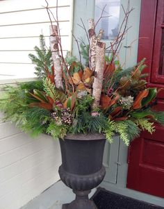 Fall urn decorated with Fall foliage that can transform into a lighted Christmas display! Love this!!