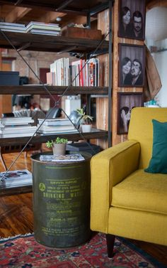 Vintage industrial. An old drinking water container serves as a side table and bookshelf as a divider in this open living area.
