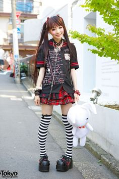 Ringo, an 18-year-old-student. Her hair is done up in twin tails with plaid bows and bangs. She is wearing a black and red top with writing print with a plaid skirt from h.NAOTO. She bought her bunny bag on Takeshita Dori and her plaid, lace and buckle shoes from Question Mark. Her accessories are from one of her favorite shops, h.NAOTO; eyeball and spider earrings, a skeleton hands choker, eyeballs bracelet, studded/leather bracelets, and striped over-the-knee socks. (Tokyo Fashion, 2014)
