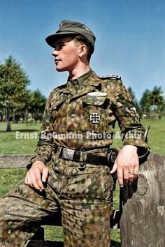 """Nice close up study of a newly issued Waffen-SS Model 44 """"Erbsentarn (pea pattern) tunic and pants being worn by an SS-Hauptscharführer (SS-Chief platoon leader) of III Battalion, SS Panzer-Grenadier Regiment """"Germania."""" It is interesting to point out that some of the men who served in this armored infantry battalion practiced a uniform style of tucking in their four pocket tunic inside the waist area of their pants give a sharper appearance. August 1944, Eastern Poland Photographer: Ernst…"""