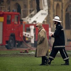 "Queen Elizabeth II surveying the scene at Windsor Castle following a fire. She dubbed the year her ""annus horribilis"" as it also saw the Princess Royal divorce and both the Duke and Duchess of York and the Prince and Princess of Wales separate."