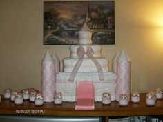 Diaper Cake Castle I made.  I wrapped the diapers around different items for each layer and secured them with skinny elastic then covered in sparkly tulle and ribbon. The bottom was the diaper box that I filled with essential goodies , the next layer is a photo box from a craft store, third layer was a tub of wipes. the top was just a group of diapers. The turrets I used a dowel to hold them up. The draw bridge was a travel wipe case wrapped in pink paper.  Turrent toppers are cardstock.