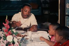 Martin Luther King Jr. Photo Gallery: Martin Luther King, Jr. serves pieces of chicken to his young sons Marty and Dexter at this 1964 Sunday dinner. (Photo:  Flip Schulke/CORBIS)