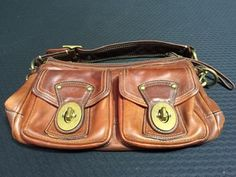 COACH THICK BROWN LEATHER SHOULDER BAG WITH BRASS HARDWARE AND COLORFUL STRIPED LINING. THERE IS A BIT OF VERDIGRIS ON THE HARDWARE AND THE LEATHER HAS A NICE PATINA FROM USE. AUTHENTICITY NOT AUTHENTICATED