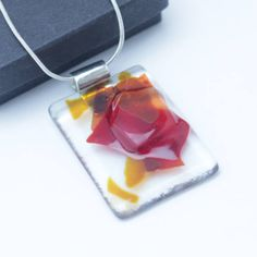 Autumn colours fused glass pendant made from recycled glass, with a silver plated chain. This elegant necklace has been made from picture frame glass with added red, brown and orange abstract elements. Clear and coloured glass is arranged and stacked in the kiln, then carefully fused together. The resulting pendant has the colours fully fused into it, but with a tactile raised glass area to it.  This pendant about 3 cm wide and 4.2 cm high (plus the bail for the chain) and is 0.3 cm thick…