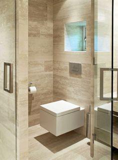 Kvadratiske former går igjen på baderommet, og toalettet er inget unntak. Det fås kjøpt hos Simas Frozen og Ha det på badet/Skøyen. Badet er kledd med Travertin Romano på både gulv, vegger og vaskebenker.