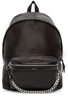 Structured grained leather backpack in black. Waxed effect throughout. Tonal grosgrain grab handle and adjustable shoulder straps at top. Wraparound zip closure at main compartment. Zippered patch pocket at bag face featuring printed logo and detachable curb chain accent. Leather logo patch at back panel. Zip pocket at interior. Black twill lining. Silver-tone hardware. Tonal stitching. Approx. 17