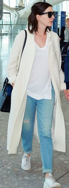 Who made Anne Hathaway's white sneakers, coat, and black tote handbag?
