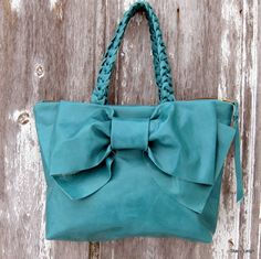 REDUCED in price. This bag has a large bow on the front. Nice and light to carry. The leather is a dark turquoise / teal color. It is smooth leather