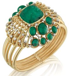 This bracelet by Mauboussin is designed as a hinged bangle bracelet, centering on a square cabochon-cut emerald, weighing approximately 34.00 carats, within a polished gold scroll surround enhanced by oval cabochon-cut emeralds and circular-cut diamonds, mounted in 18K yellow gold. (Via Phillips).